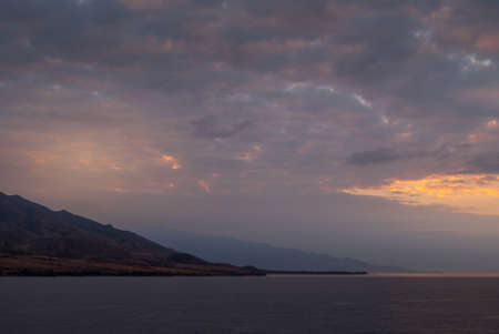Lahaina, Maui, Hawaii, USA. - January 12 2012: Early morning light over ocean while approacing West side on dark ocean under spectacular cloudscape as if heaven is on fire. Shape of coastline hills. Banco de Imagens