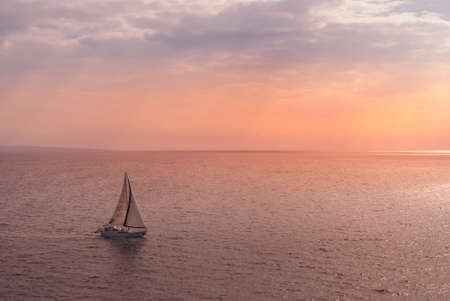 Lahaina, Maui, Hawaii, USA. - January 12 2012: Small sail boat on pink to orange ocean under pink to blue early morning sky. Banco de Imagens