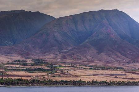 Lahaina, Maui, Hawaii, USA. - January 12 2012: West coast  ocean shoreline shows brown-yellow dry meadows, houses along beach and dark mountain range under massive gray cloudscape.