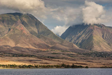Lahaina, Maui, Hawaii, USA. - January 12 2012: West coast dark ocean shoreline shows brown-yellow dry meadows, a town and 2 dark gray-brown mountains under cloudscape. Banco de Imagens
