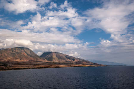 Lahaina, Maui, Hawaii, USA. - January 12 2012: Long shot on West coast dark ocean shoreline shows brown-yellow dry meadows, a town and 2 dark green-brown mountains under blue cloudscape.