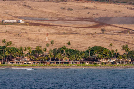 Lahaina, Maui, Hawaii, USA. - January 12 2012: Residential housing set in green belt along blue ocean, in front of brown dry agricultural land.