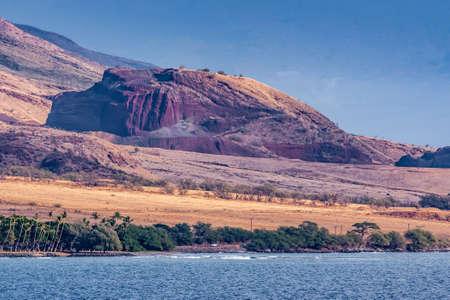 Lahaina, Maui, Hawaii, USA. - January 12 2012: Volcanic plug boulder in brown dry landscape under blue sky with green belt along blue ocean shoreline.