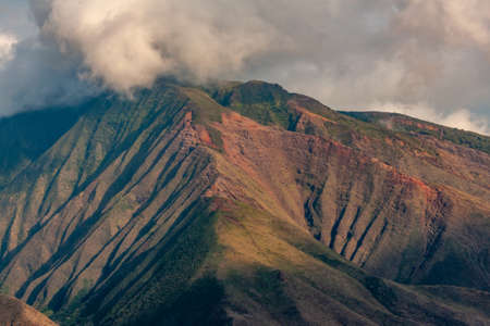 Lahaina, Maui, Hawaii, USA. - January 12 2012: Closeup of green-brown mountain, part of Haleakala volcano range under thick gray-white cloudscape. Banco de Imagens