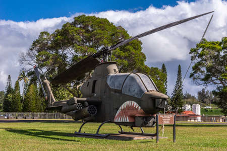Oahu, Hawaii, USA. - January 10, 2012: Wheeler Air Force Base. Historic Cobra Bell helicopter on display on green lawn and green trees in back under blue heavy cloudscape. Editorial