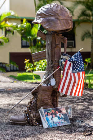 Oahu, Hawaii, USA. - January 10, 2012: Bronze helmet on rifle fallen soldier statue as part of United In Sacrifice group statue at Schofield Barracks of Army 25th Infantry Division. Flag, picture and green vegetation.