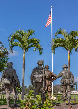 Oahu, Hawaii, USA. - January 10, 2012: United In Sacrifice group statue seen from back in front of US flag under blue skay at Schofield Barracks of Army 25th Infantry Division. Publikacyjne