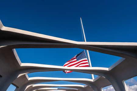 Oahu, Hawaii, USA. - January 10, 2012: Pearl Harbor. US Flag half pole over USS Arizona against blue sky. Seen through open ceiling of memorial.
