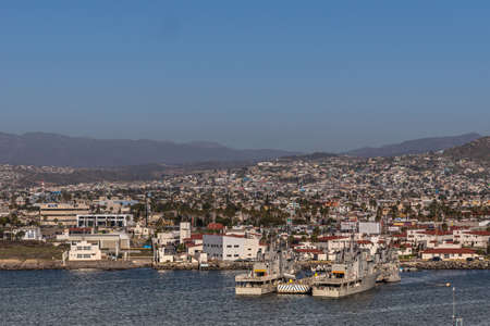 Ensenada, Mexico - January 17, 2012: Monasterio and Blanco gray navy vessels in port  on blue bay water with cityscape in back under blue sky and hazy mountains.