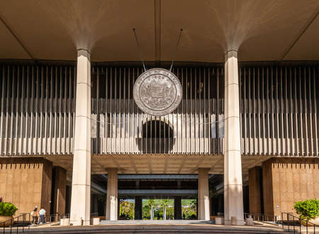 Honolulu  Oahu, Hawaii, USA. - January 10, 2012: Bronze Seal of   State of Hawaii hangs from ceiling above entrance to State Capitol. Sun shines on the subject. Editorial