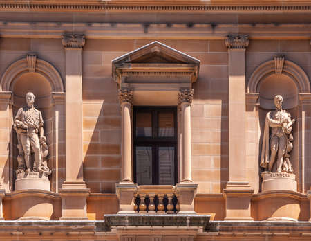 Sydney, Australia - December 11, 2009: Closeup of red-stone facade of Lands Department Building with statues of Hume and Flinders.