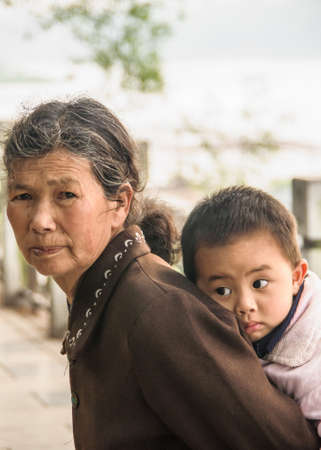 Guilin, China - May 11, 2010: Downtown. Closeup of grandmother in brown garb carrying young boy on her back.