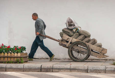 Guilin, China - May 11, 2010: Downtown. Man pulls wooden cart full of gray bags on sidewalk with a white wall as backdrop and red flowers in green patch. Publikacyjne