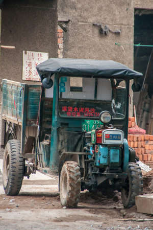 Guilin, China - May 11, 2010: Downtown. Green-blue small tractor with exposed motors at construction site with pile of red bricks.