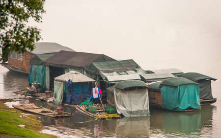 Guilin, China - May 11, 2010: Downtown. Migrant worker housing, shack and tent like, built on rafts on greenish Li River near green shore in fog.