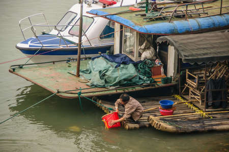 Guilin, China - May 11, 2010: Downtown. Different house boats docked along Li River. On the bamboo one, a man fills red bucket with greenish water.