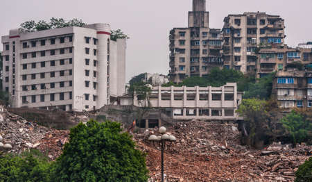 Chongqing, China - May 9, 2010: Downtown, off Peoples Square. Huge demolition rubble site with old and newer buildings in back and some green foliage.