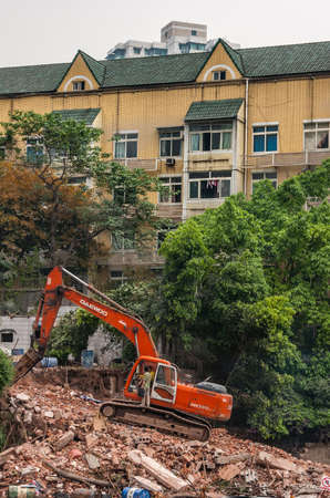 Chongqing, China - May 9, 2010: Downtown, off Peoples Square. Red Daewoo demolition crane on top of pile of stone rubble. Green foliage and yellow building in back. Workers present. Publikacyjne