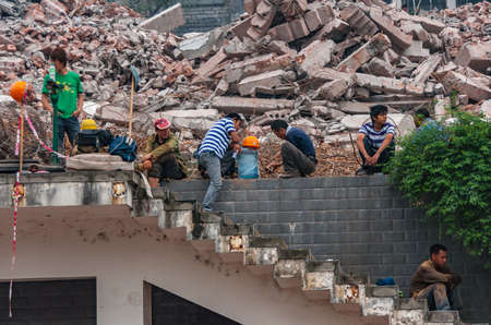 Chongqing, China - May 9, 2010: Downtown, off Peoples Square. Demolition crew take lunch break on top of pile of stone rubble.
