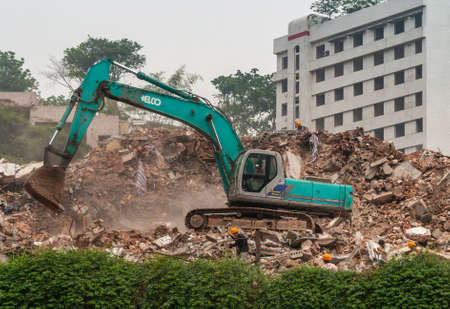 Chongqing, China - May 9, 2010: Downtown, off Peoples Square. Green Kobelco demolition crane on top of pile of stone rubble. Green foliage and white building in back. Workers present.
