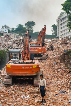 Chongqing, China - May 9, 2010: Downtown, off Peoples Square. Red Daewoo and Hitachi demolition craned on top of pile of stone rubble. Workers present.