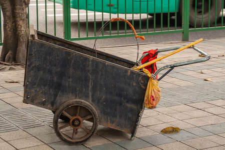 Chongqing, China - May 9, 2010: Downtown. Closeup of Black box push cart to collect trash and garbage in street. Yellow broom stick and red safety vest. Green fence in back.