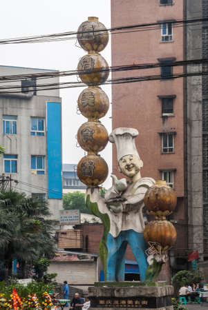 Chongqing, China - May 9, 2010: Downtown. Closeup of statue of chef in white and blue juggling brown balls. Electircal cables and dirty facades of residential buildings under silver sky.
