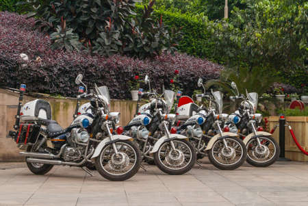 Chongqing, China - May 9, 2010: Downtown. Closeup of 4 parked identical Police motorcycles with red and green foliage in back. Publikacyjne