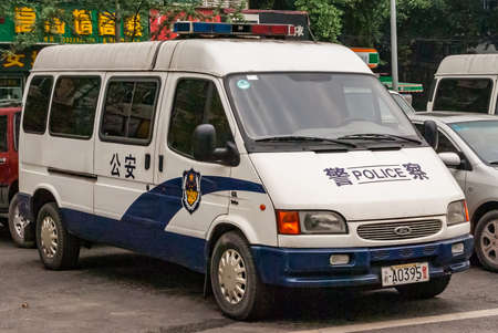 Chongqing, China - May 9, 2010: Downtown. Closeup of white parket Police van with green foliage in back. parts of other cars and yellow mandarin symbols on green.