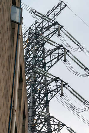 Chongqing, China - May 9, 2010: Downtown. Closeup of dark gray high voltage electrical pylon cable fixtures against light blue sky along brown facade.