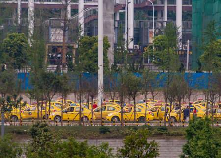 Chongqing, China - May 9, 2010: Downtown. Lines of yellow taxis seen through screen of green foliage in front of facade of tall transport hub.