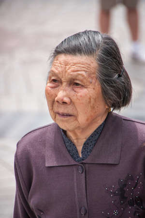 Shanghai, China - May 4, 2010: Closeup of face of older graying senior woman dressed in purple garb. Editorial