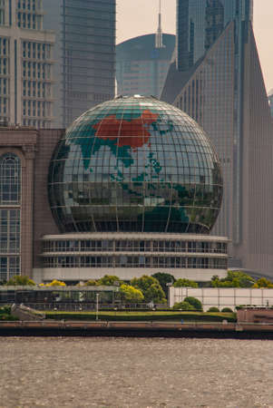 Shanghai, Pudong, Lujiazui, China - May 4, 2010: Giant glass globe replica on side of International Conference Center. Parts of skyscrapers in back. Green foliage at bottom near Huangpu River. Editorial