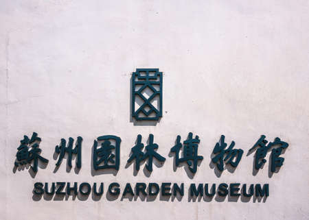 Suzhou China - May 3, 2010: Closeup of Black letters and symbols on white wall for Suzhou Garden Museum. Sun provokes shadows.