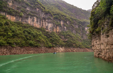Wuchan, China - May 7, 2010: Dawu or Misty Gorge on Daning River. Bend in canyon with brown rocky cliffs, green foliage on top and small boat on emerald green water. Banco de Imagens