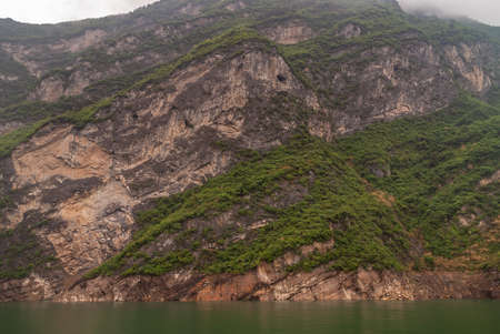 Xiangxicun, China - May 6, 2010: Xiling gorge on Yangtze River. Brown-black cliffs with green covered tops and some caves in flanks behind emerald green water. Foggy cloudscape peeps over mountains.