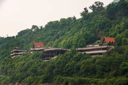 Fengdu, Chongqing, China - May 8, 2010: Yangtze River. Classic architecture style red roofs popping above green forest on hill slope at large monstery. Some silver sky.