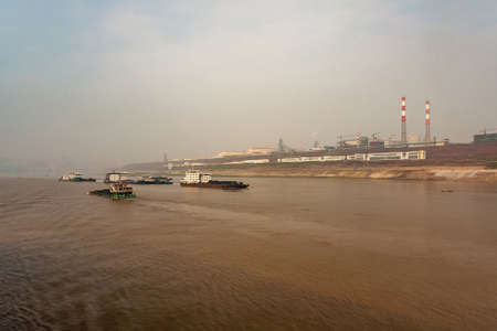 Chongqing, China - May 8, 2010: Yangtze River. Giant power plant and factories on shoreline behind wide brown water with several coal transporting boats under light blue sky.