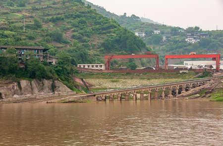 Myaoyinan, Chongqing, China - May 8, 2010: Yangtze River. Slipway and large crane bridges behind brown water, at Chiandong Shipyard. Green Mountain slope with agriculture plots in back.