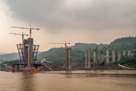 Fengdu, Chongqing, China - May 8, 2010: Yangtze River. Concrete suspension towers for bridge under construction with tall yellow cranes over brown water, cloudscape and green hill.