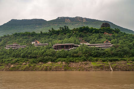 Fengdu, Chongqing, China - May 8, 2010: Yangtze River. Classic architecture style red roofs popping above green forest on hill slope at large monstery. Some silver cloudscape.