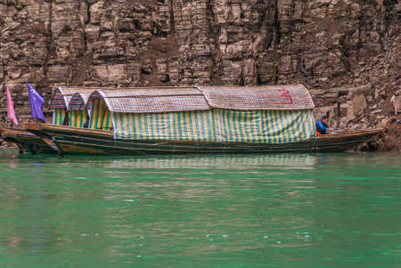 Wushan, Chongqing, China - May 7, 2010: Mini Three Gorges. 3 covered tourist sampans with captain docked against brown cliff rock  behind emerald green water. Flags add color. 新聞圖片