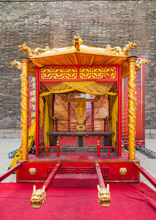 Yellow-red-gold gestatorial queen and king throne on display behind red carpet at gate.