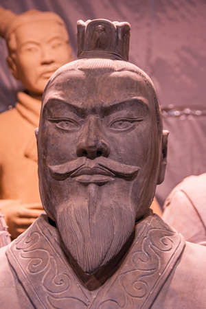 Xian, China - May 1, 2010: Terracotta Army museuml.  Closeup of reddish bearded head of officer sculpture with another one in faded back. Editorial