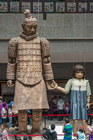 Xian, China - May 1, 2010: Terracotta Army museuml.  Giant light brown sculpture of officer in style holding hand of girl doll about half his size. People around.