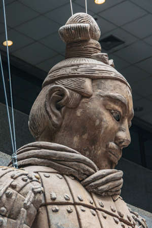 Xian, China - May 1, 2010: Terracotta Army museuml.  Head closeup of Giant light brown sculpture of officer in style. Ceiling as backdrop. Editorial