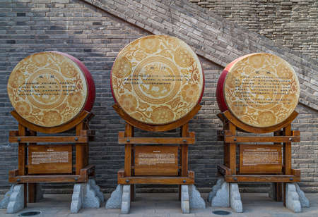 Xian, China - April 30, 2010: North Gate of Huancheng City Wall. 3 war drums on display at gate with historic explanation texts.