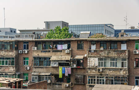 Xian, China - May 1, 2010: Old residential brown brick housing with dilapidated balconies, AC systems and laundry hanging to dry under silver sky.