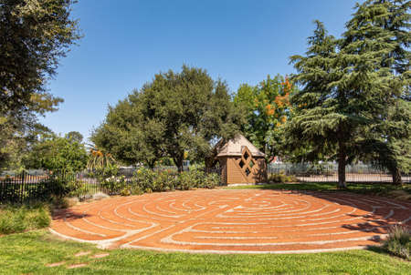 Los Olivos, California, USA - September 3, 2020: Orange dirt and light gray stone forms labyrinth or Zen circle outside  St. Marks in the Valley Church. Green tree foliage surrounds it under blue sky.