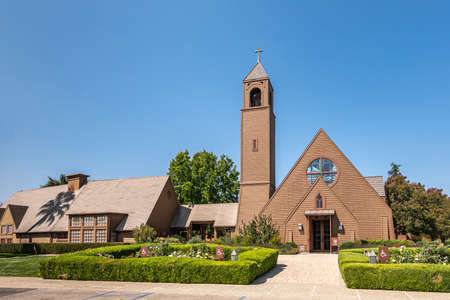 Los Olivos, California, USA - September 3, 2020: Frontal viw on brown wood St. Marks in the Valley Church with bell tower set in green park under blue sky, including side buildings.